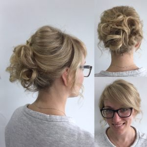 woman smiling wearing glasses with bun hairstyle