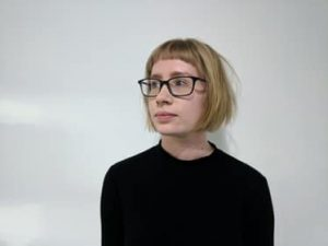 woman wearing glasses with short blonde hair with fringe