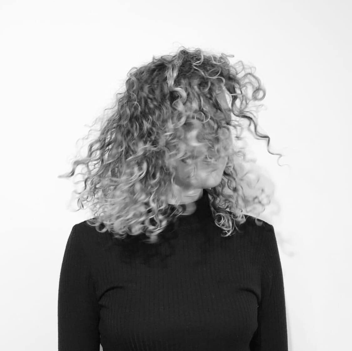 black and white photo of woman with curly hair