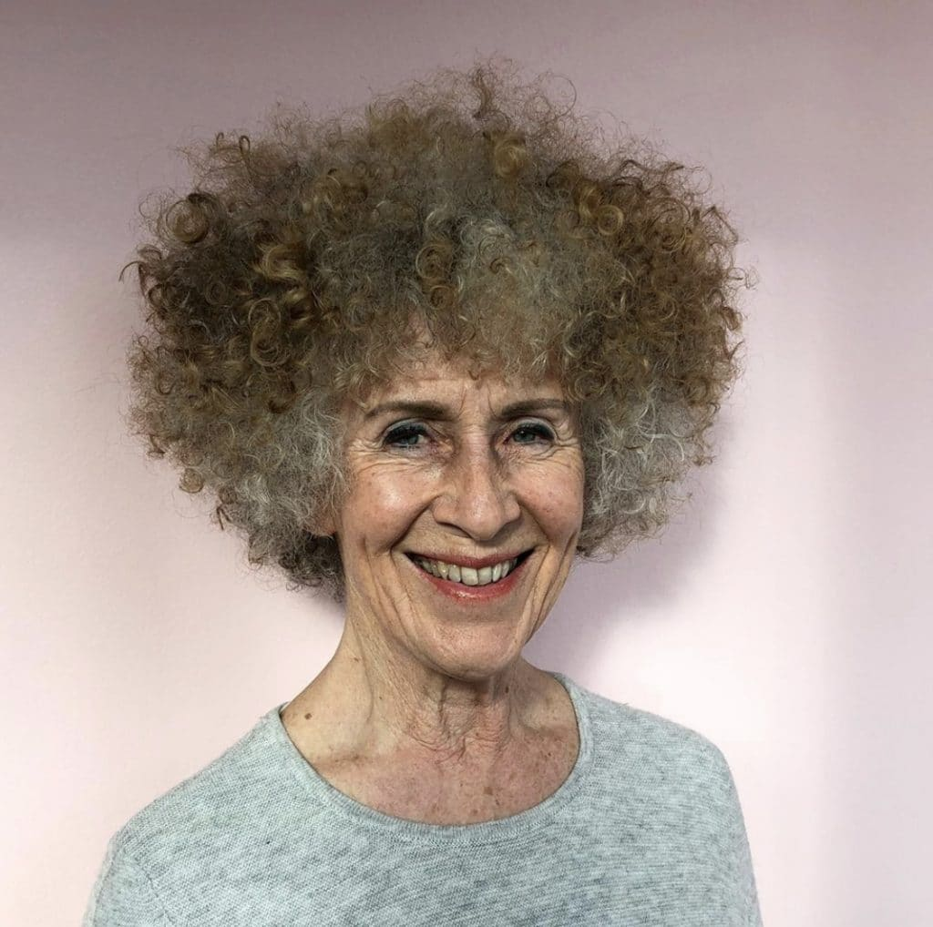 mature woman smiling with curly hair